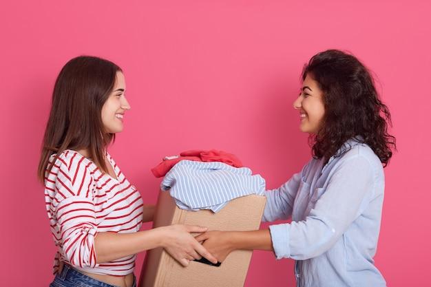Twee aantrekkelijke vrouwen poseren geïsoleerd op roze achtergrond