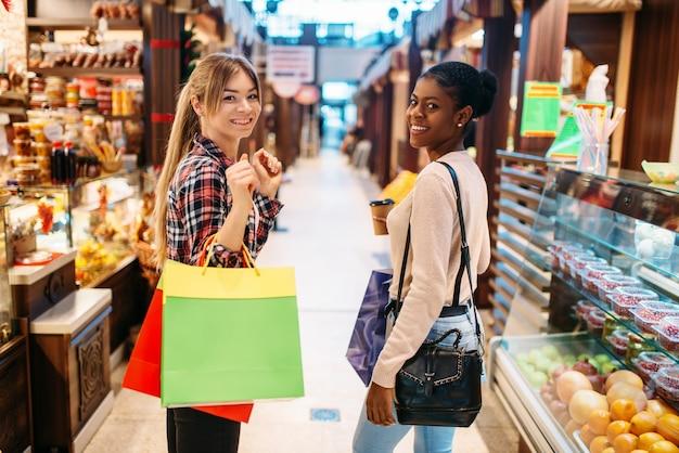Twee aantrekkelijke vrouwtjes in food-court na het winkelen.