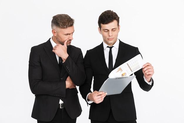 Twee aantrekkelijke zelfverzekerde zakenlieden die pakken dragen die geïsoleerd staan en een nieuw project bespreken