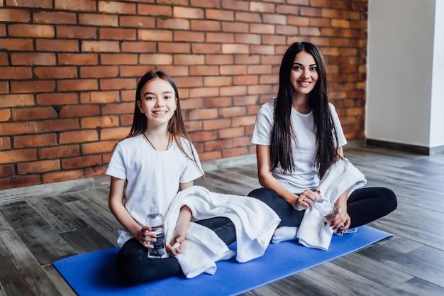Twee aantrekkelijke zusters met handdoek op water na yoga tijd
