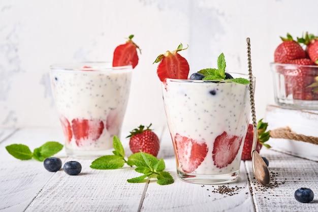 Twee aardbeichiazaden gelaagde smoothie of milkshake met aardbei en bosbessenmunt in glas op lichtgrijze achtergrond. zomer en gezonde dieetdranken, vegetarisch voedselconcept.