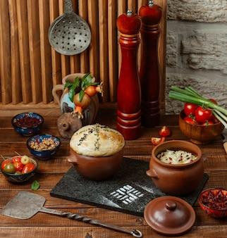 Twee aardewerken potten met rijst en deegkorst, geserveerd met augurken