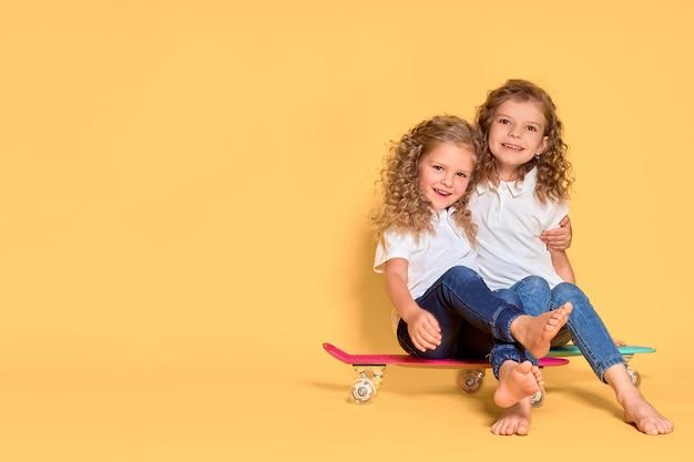 Twee actieve en gelukkige meisjes met krullend haar met plezier met cent board,