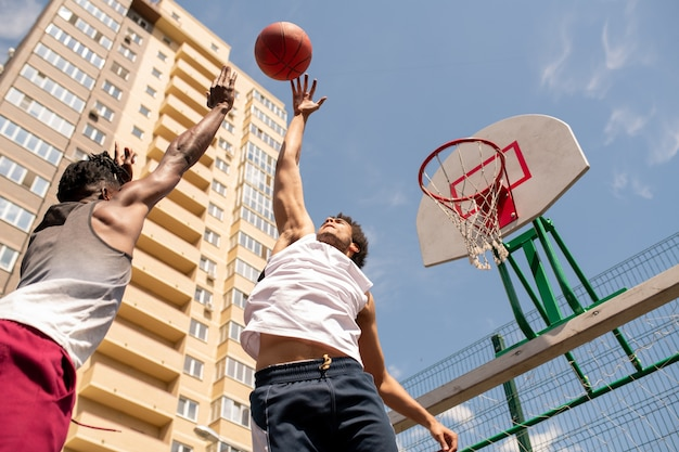 Twee actieve jongens in sportkleding die vliegende bal proberen te vangen tijdens het spelen van basketbal in een stedelijke omgeving