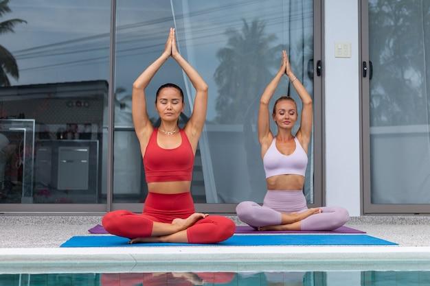 Twee actieve vrouw aziatische en kaukasische beoefenen van yoga bij het zwembad van de luxevilla