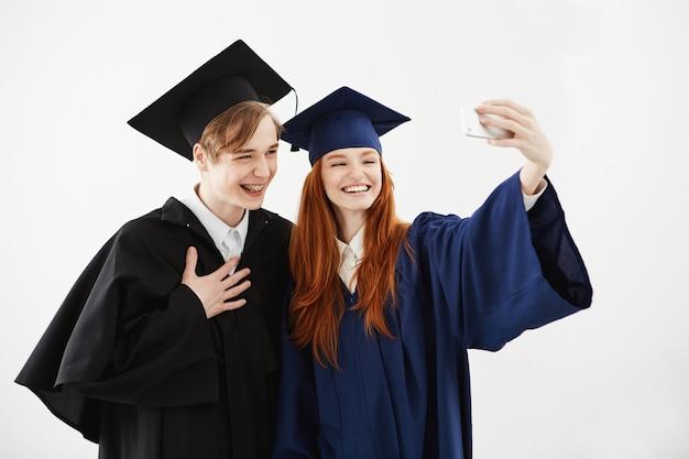 Twee afgestudeerde vrienden in petten en mantels lachen en maken selfie voordat ze hun magister-diploma of bachelor of arts of een andere academische graad ontvangen. studie concept.