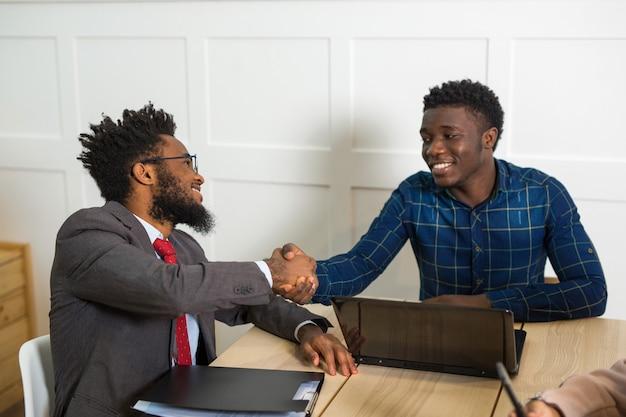 Twee afrikaanse mannen aan tafel schudden elkaar de hand