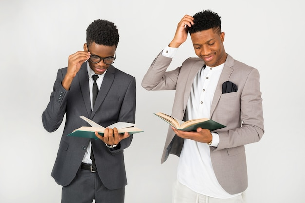Twee afrikaanse mannen in pakken met boeken