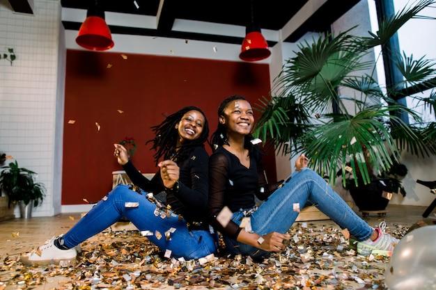 Twee afrikaanse meisjes, gelukkige stijlvolle vrienden die nieuwjaar vieren of verjaardagsfeestje leun achterover met elkaar en gooi een confetti. mode elegantie vrouwen genieten van tijd samen.