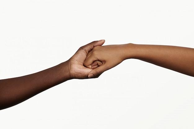 Twee afrikaanse mensen die hun handen stevig tegen elkaar houden.