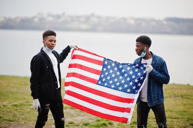 Twee afrikaanse tienersvrienden met amerikaanse vlag bij park die medische maskers dragen beschermen tegen infecties en de quarantaine van het coronavirusvirus.
