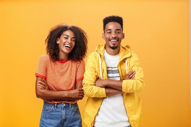 Twee afro-amerikaanse man en vrouw zijn beste vrienden die hardop lachen terwijl ze naar grappige films in de bioscoop kijken, allemaal gekleed in een stijlvolle outfit. staande met de handen gekruist op de borst en geamuseerde uitdrukking.