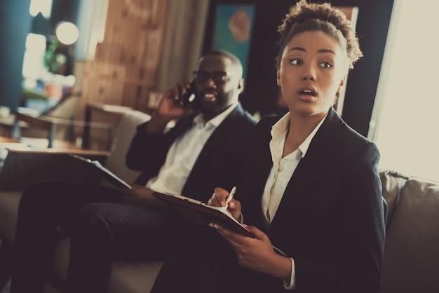 Twee afro-amerikaanse managers zitten op de bank.