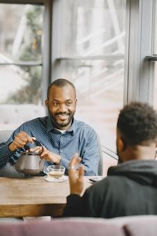 Twee afro-amerikaanse mannen in gesprek met een kopje thee. vriend zit in een café.