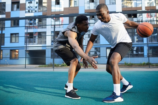Twee afro-amerikaanse mannen spelen basketbal