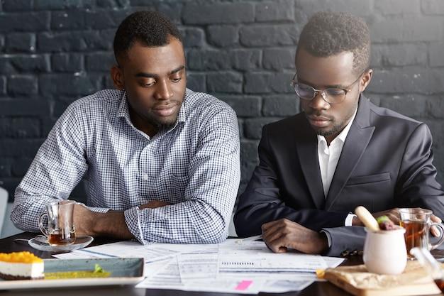 Twee afro-amerikaanse professionals met formele bijeenkomst op modern kantoor