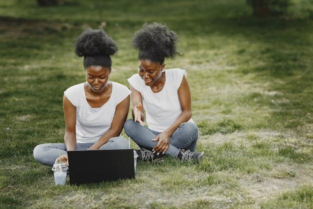 Twee afro-amerikaanse zussen rusten uit in een park