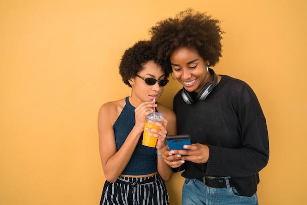 Twee afro-vrienden met behulp van hun mobiele telefoon.