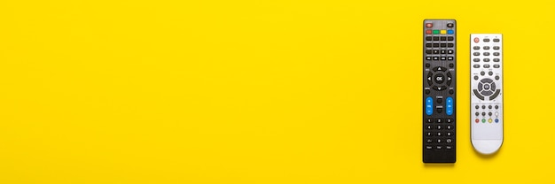 Twee afstandsbedieningen van de tv, tv-tuner op geel