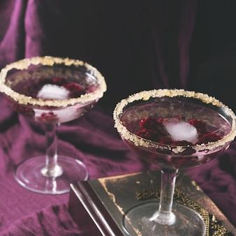 Twee alcoholcocktails met bessen op paars. vierkant afgezwakt