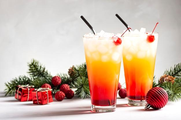 Twee alcoholische cocktails sunrise met tequila staan in de buurt van fir takken op een grijze achtergrond
