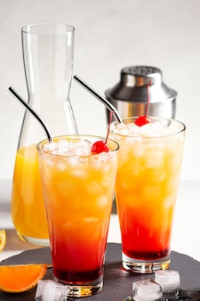Twee alcoholische cocktails tequila sunrise met ijs op een grijze betonnen achtergrond