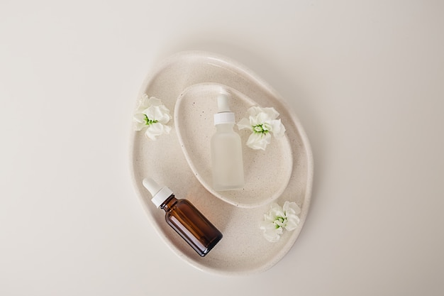 Twee amberkleurige en matte glazen flessen voor cosmetica, natuurlijke geneeskunde, etherische olie in avocado-vormige keramische platen versierd met bloemen op een witte achtergrond. bovenaanzicht, schoonheidsproduct plat.