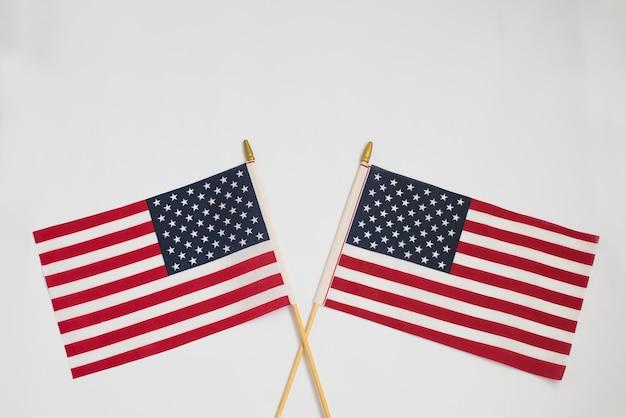 Twee amerikaanse vlaggen die elkaar op wit kruisen