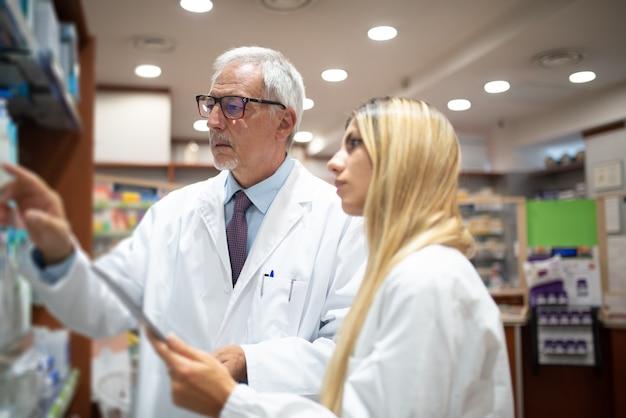 Twee apothekers controleren hun inventaris in hun apotheek