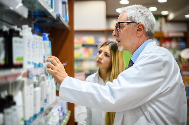 Twee apothekers, man en vrouw, op zoek naar een product op een plank