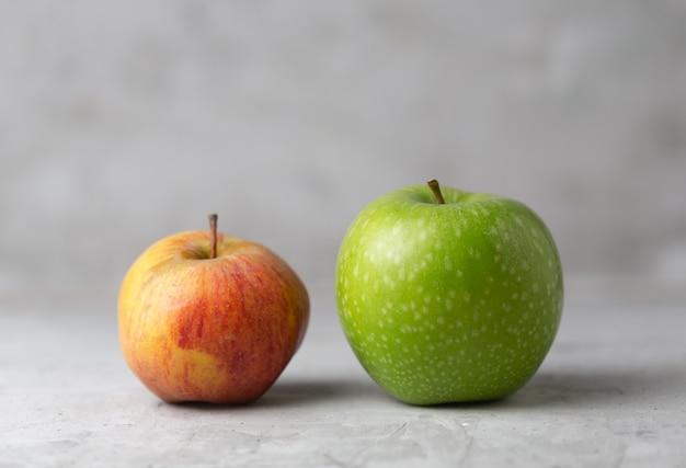 Twee appels op een grijze betonnen verticaal