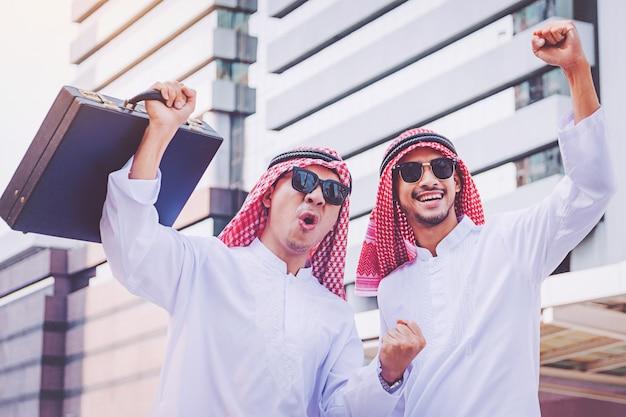 Twee arabische zakenlieden die door beide handen omhoog in stad opheffen te bevinden