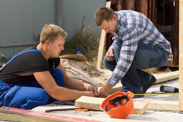 Twee arbeiders aan het werk op een bouwplaats die isolatiepanelen meten voor installatie op de hoek van een nieuwbouwhuis