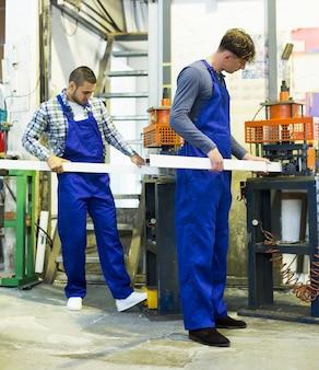 Twee arbeiders die aan een machine werken