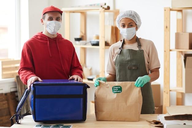 Twee arbeiders dragen maskers bij het inpakken van bestellingen bij contactloze bezorgservice voor eten