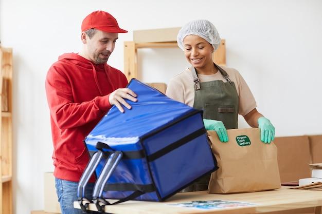 Twee arbeiders glimlachen terwijl ze bestellingen inpakken bij de bezorgservice voor eten