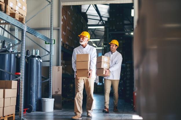 Twee arbeiders in witte uniformen en met gele helmen op hun hoofd verplaatsen zware dozen in het magazijn.