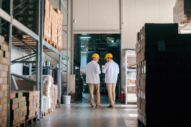 Twee arbeiders lopen in de opslag. dozen op planken. teruggedraaid.