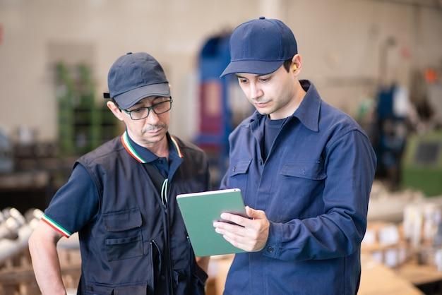 Twee arbeiders met behulp van een tablet in een moderne fabriek