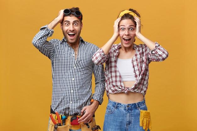 Twee arbeiders van de onderhoudsdienst poseren voor de gele muur, kijken opgewonden, raken hoofden aan en schreeuwen met wijd open mond. concept voor reparatie, verbouwing en renovatie
