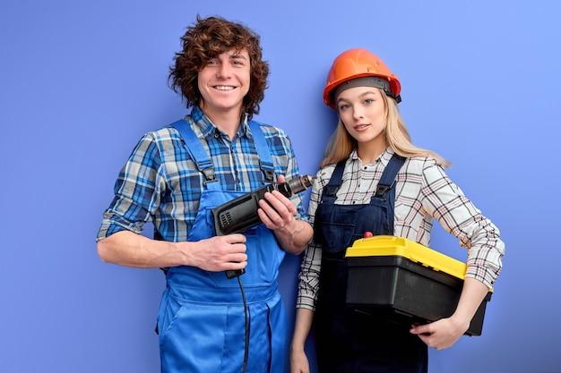 Twee architecten in uniforme overall staan met tools instrumenten poseren geïsoleerd op blauw