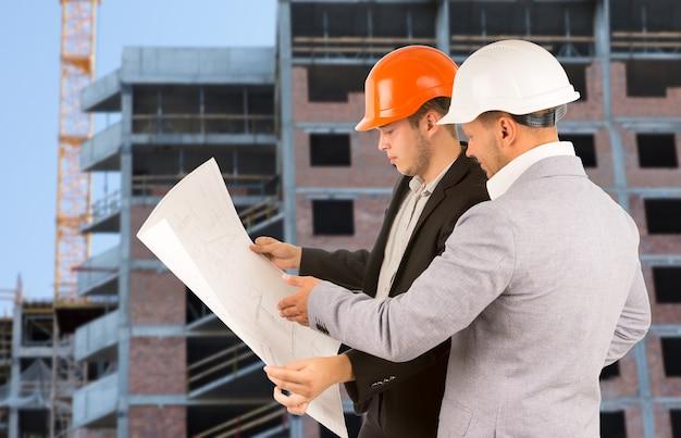 Twee architecten of ingenieurs die staan te praten over een bouwblauwdruk