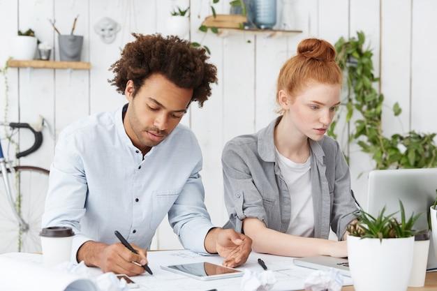 Twee architectenmedewerkers werken hard, met een deadline