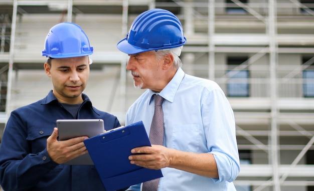 Twee architectenontwikkelaars beoordelen bouwplannen op de bouwplaats met behulp van een tablet