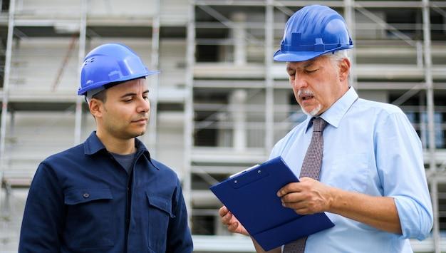 Twee architectenontwikkelaars beoordelen bouwplannen op de bouwplaats