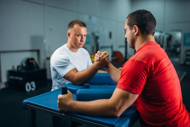 Twee armworstelaars aan tafel met pinnen, trainen voor worstelwedstrijd.