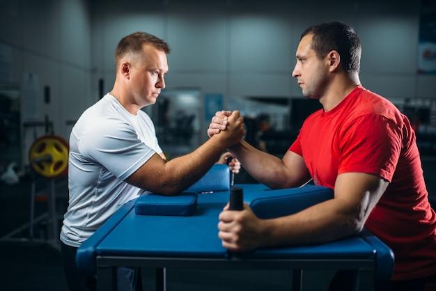 Twee armworstelaars op startpositie, worstelen
