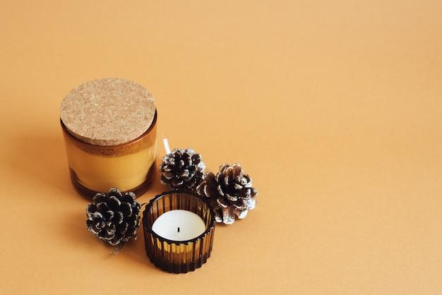 Twee aromakaarsen en decoratieve denneappels op oranje achtergrond