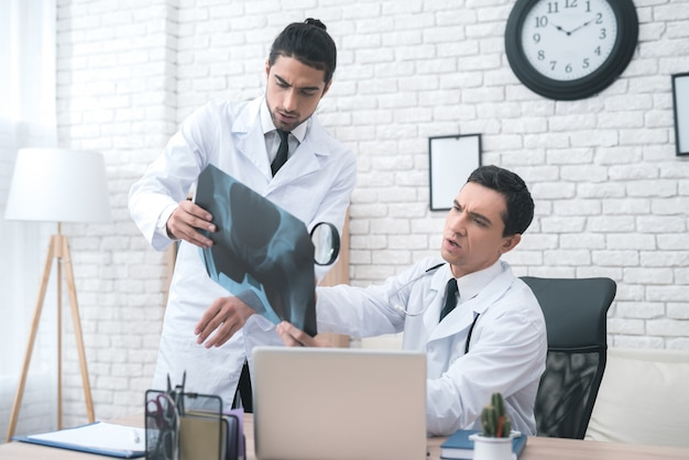 Twee artsen bekijken de röntgenstraal in het medische kantoor.