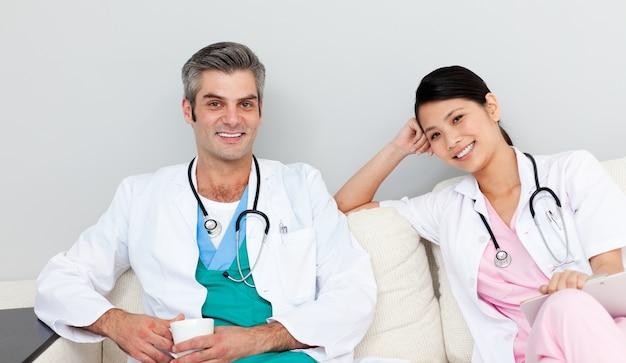 Twee artsen die en koffie ontspannen drinken